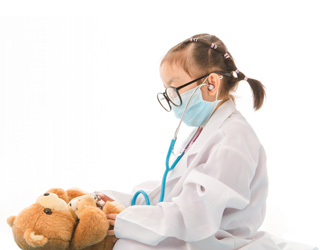 A child dressed as a doctor inspects a stuffed bear