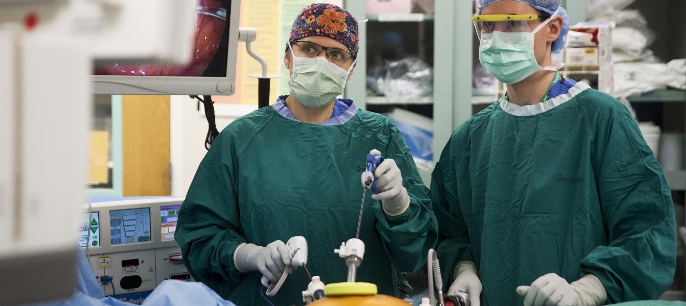 Julie Thacker, MD, left, and surgical resident Paul Speicher perform surgery at Duke University Hospital.