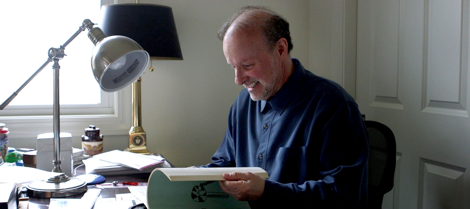Blaine Hall looks through a book containing one of his poems