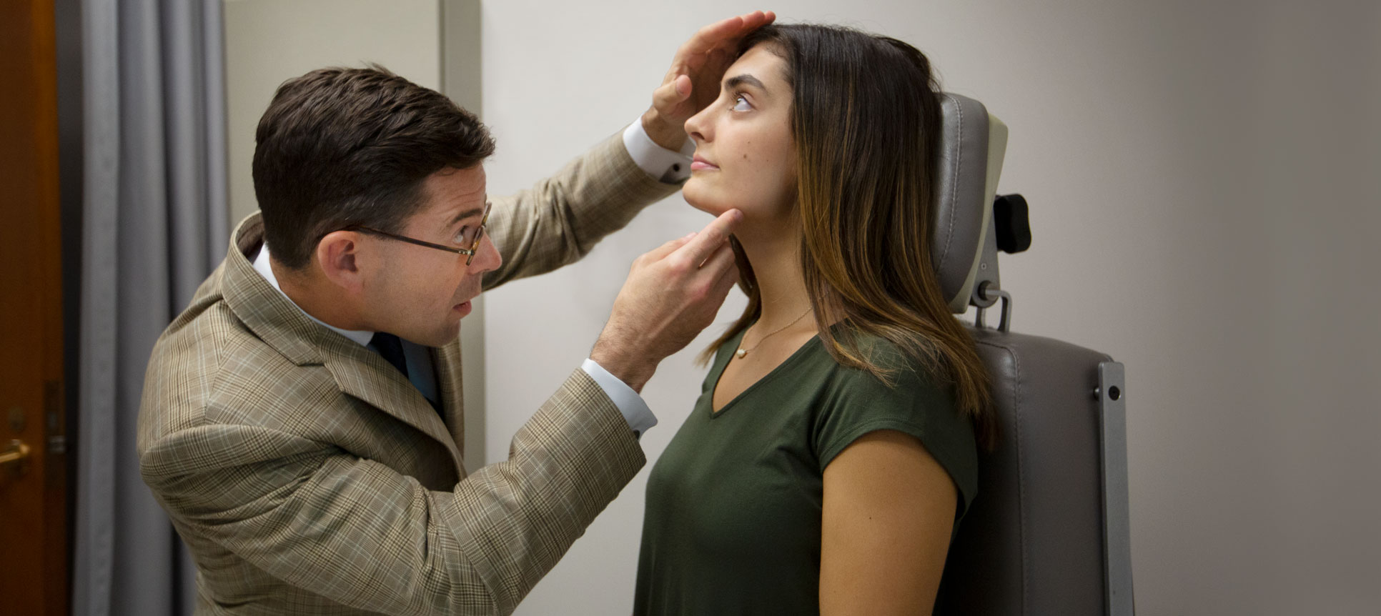 A doctor looks at a patient's nose