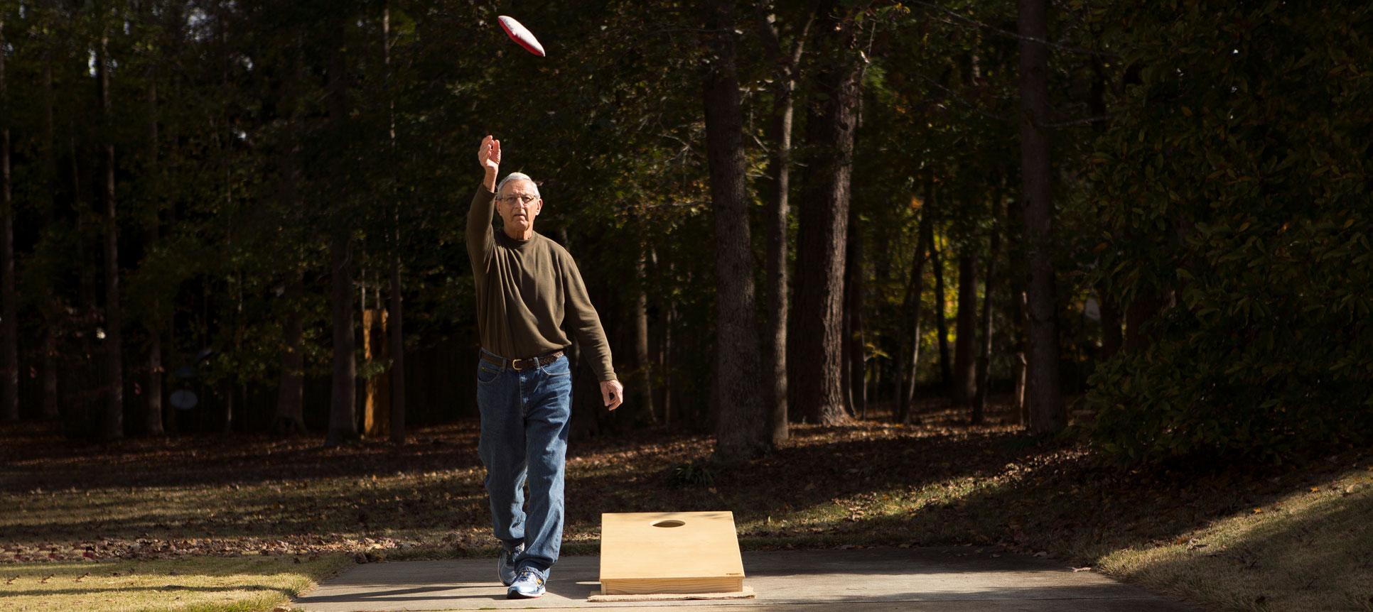 Dick Mazur tosses a cornhole bag.