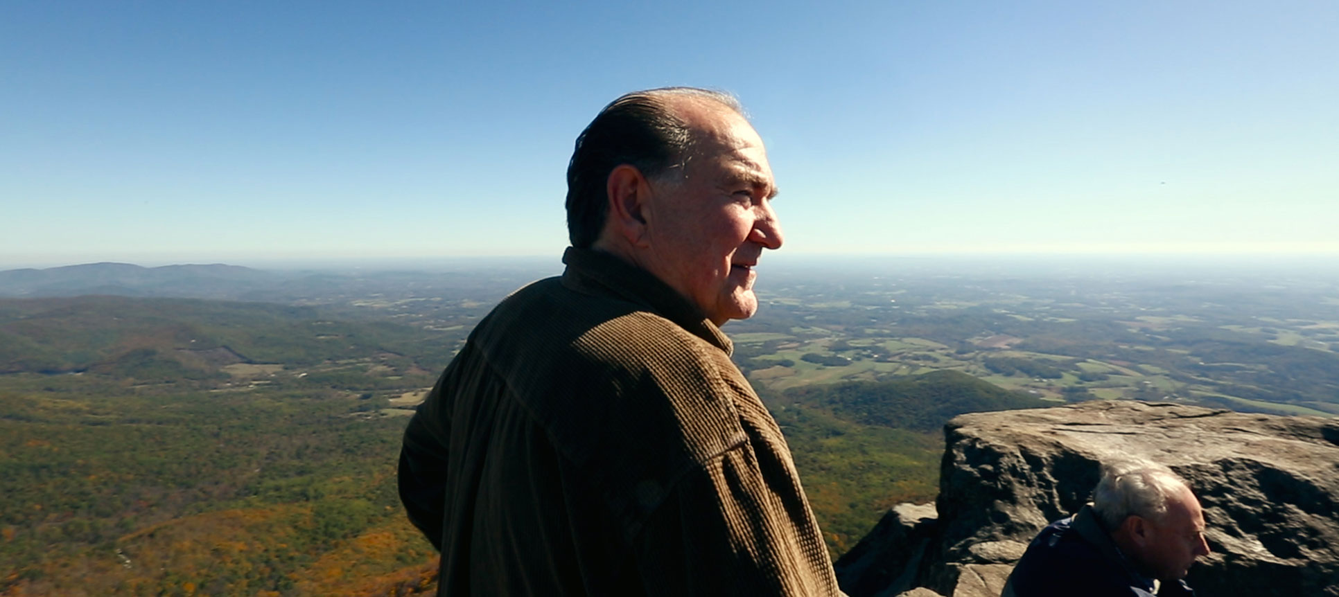 Jim Ashwell stands at the top of a mountain.