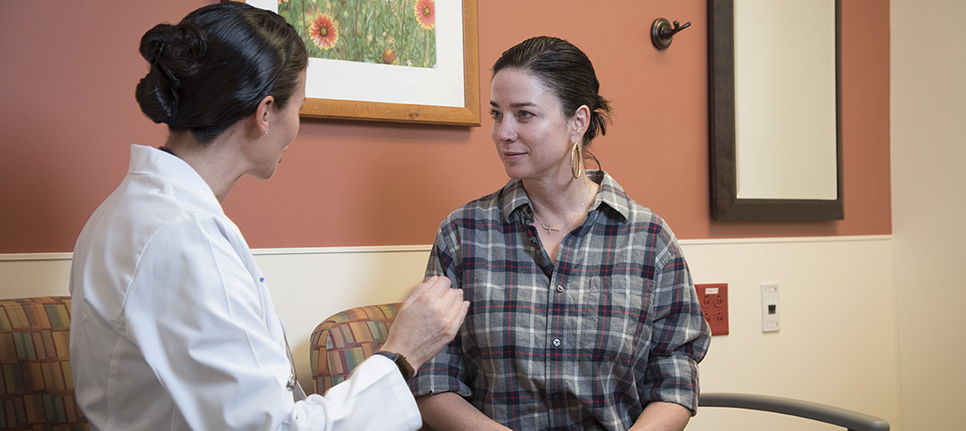 Breast surgical oncologist Jennifer Plichta, MD, counsels Shanel Wilson-Poe on her breast cancer risk.