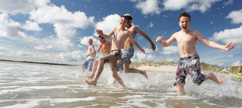 Group of boys running and splashing in the ocean