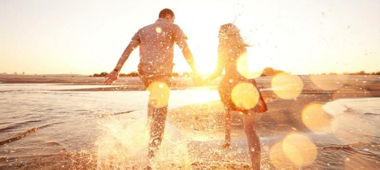 Man and woman running into the ocean