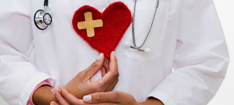 Doctor holding a decorative heart made of red felt fabric