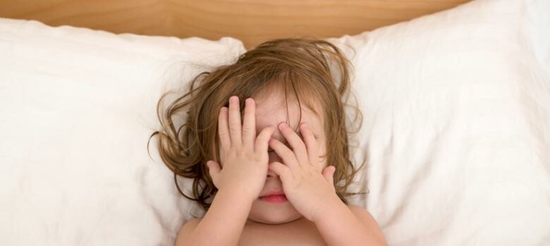 Child in bed with his hands on his face