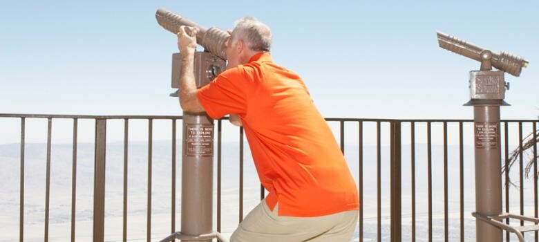 Man looking through an observation telescope