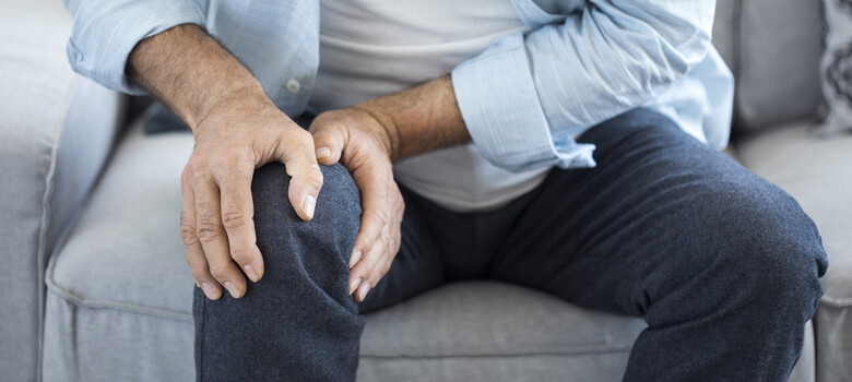 A man holds his knee, seemingly in pain