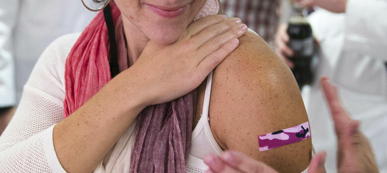 Woman getting bandaid placed after flu vaccination
