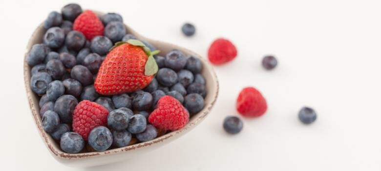 blueberries and strawberries in a heart-shaped bowl
