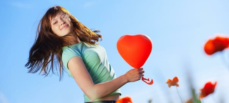 Woman holding heart-shaped balloon