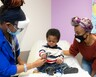 A provider shows a young male patient her stethoscope as the patient's mother watches