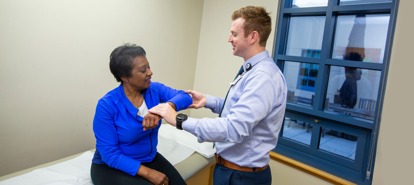 A provider looks at a patient's shoulder