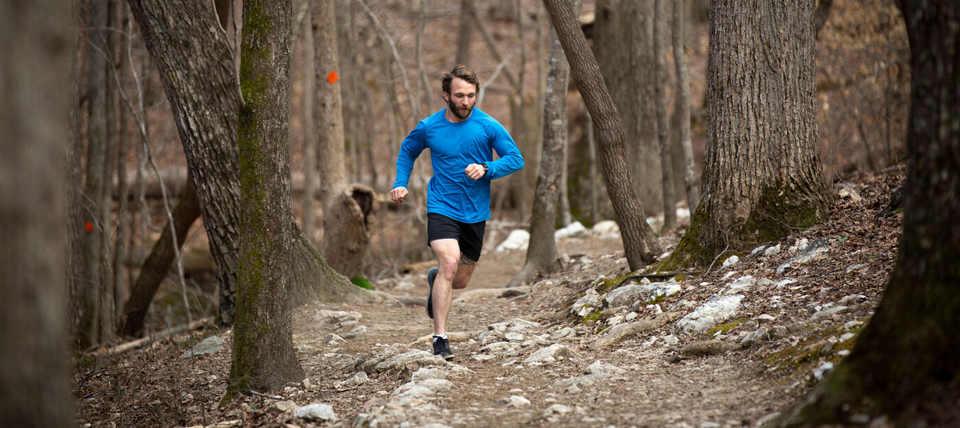 a man goes for a run through the woods