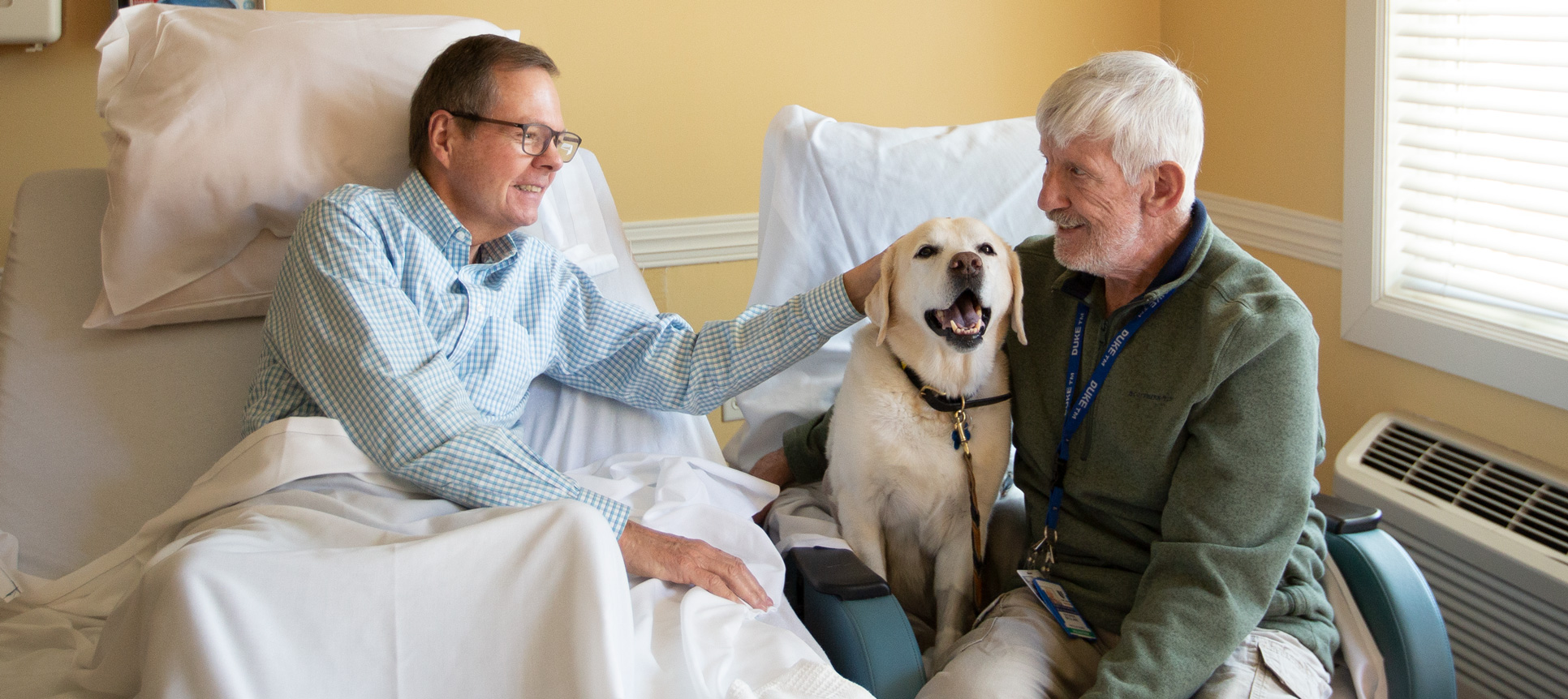 A volunteer and a dog visit a patient