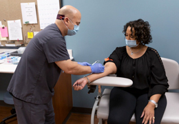 A provider draws blood from a patient